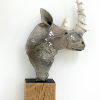 Rhino bust textile art sculpture on oak. Barbed wire horn, animal rights.