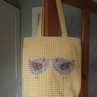 Yellow gingham tote bag with phone case inside and birds on the front