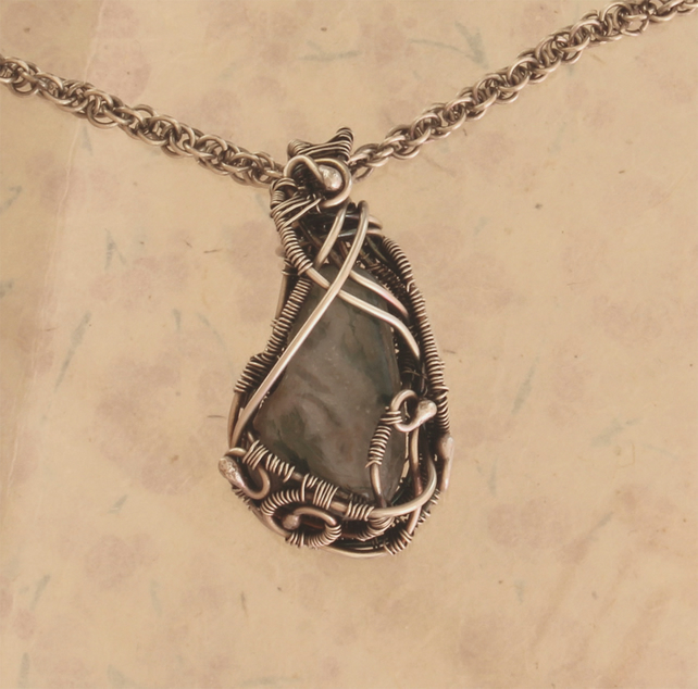 Celt statement pendant, moss agate caressed in silver curves on loose coil chain