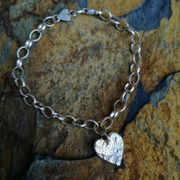 Silver bracelet with a heart charm.