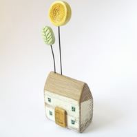 Little wooden house with yellow clay sunflower