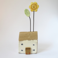 Little wooden house with yellow flower