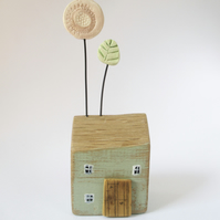 Little wooden house with a clay flower and leaf