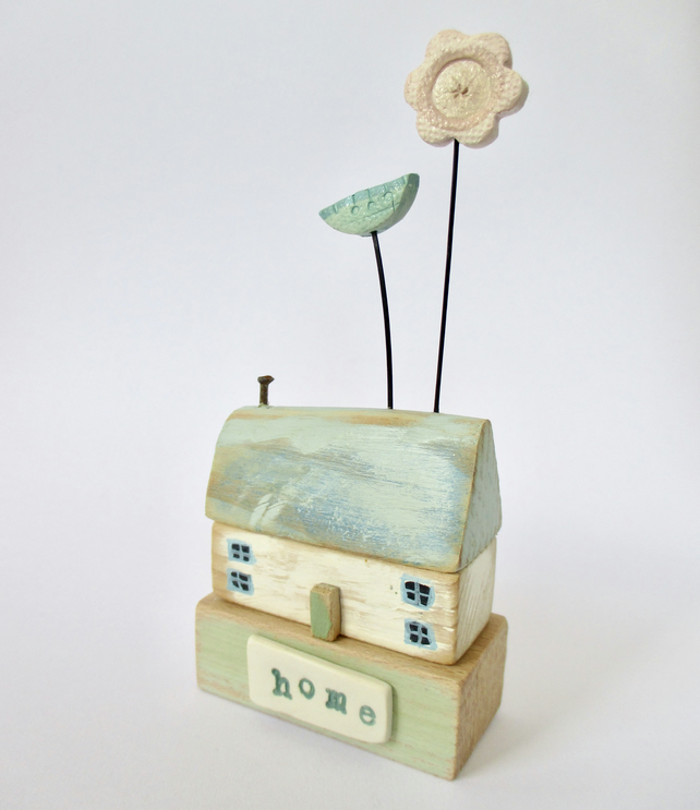 Little wooden home with two clay flowers