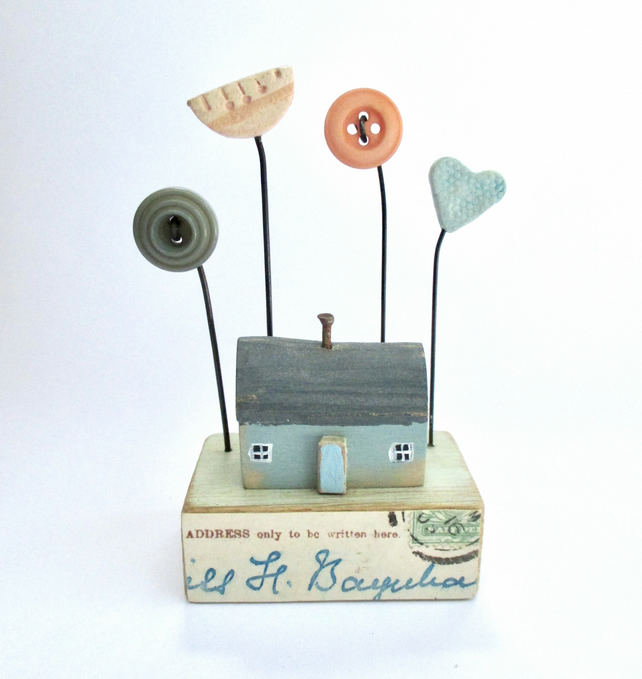 Little wooden painted house with buttons, flower and clay heart garden