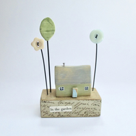 Little wooden home with a clay tree and button flowers