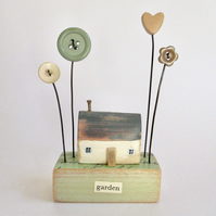 Little wooden painted house with buttons and clay heart garden