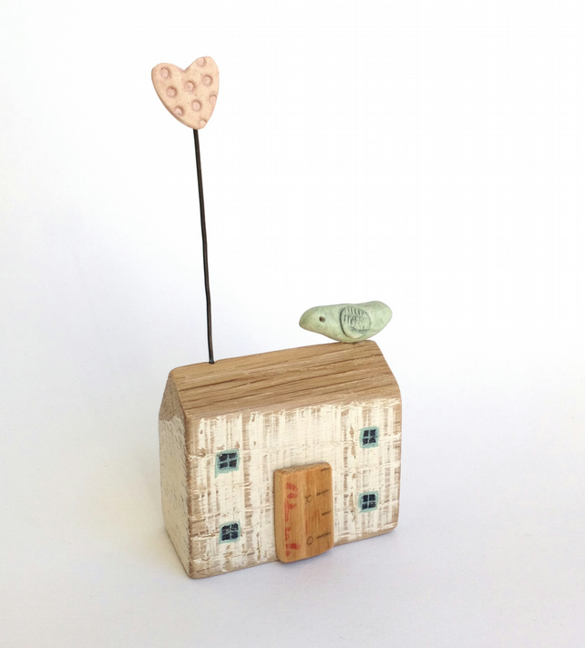 Little wooden house with clay heart and bird