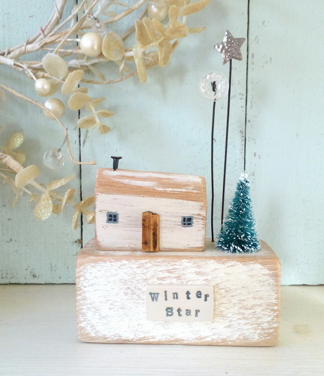 Little wooden house with Christmas tree, button and star