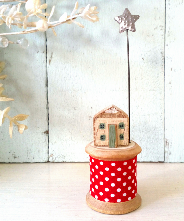 Little wooden house with Christmas star on vintage bobbin