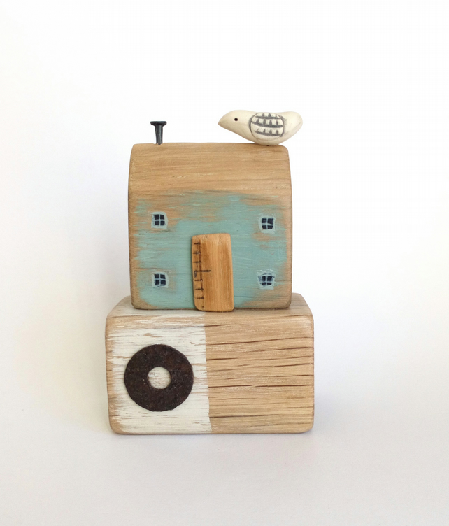 Little wooden seaside house with clay bird