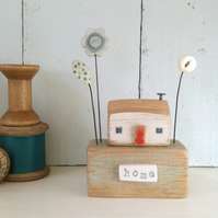 Little wooden house with clay and button flowers