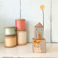 Little wooden house with clay flower on a vintage toy block