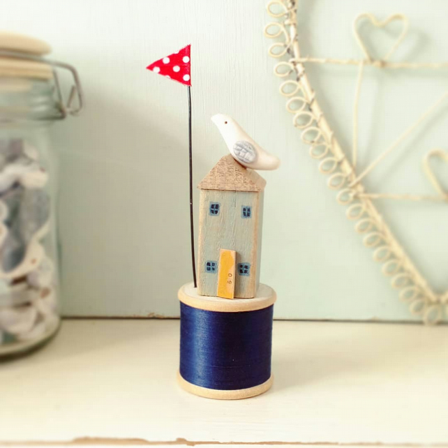 Little sea house with clay seabird on wooden bobbin