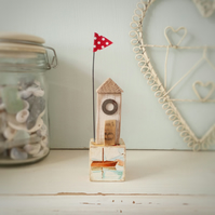 Little wooden sea house with flag on a vintage toy block