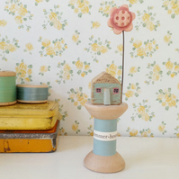 Little oak house with clay flower on wooden bobbin 'summer-house'