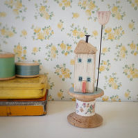 Little oak house with clay flower on wooden bobbin