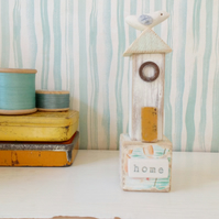 Little wooden beach hut with clay bird on a vintage toy block