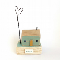 Little wooden house with a wire love heart