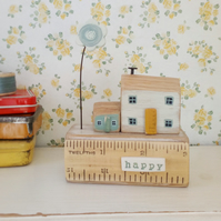Little happy wooden houses with clay flower on a vintage ruler block