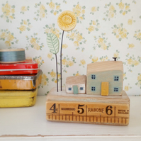 Little wooden houses with clay sunflower on a vintage ruler block