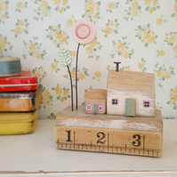 Little wooden houses with clay flower on a vintage ruler block