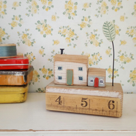 Little wooden houses with clay tree on a vintage ruler block