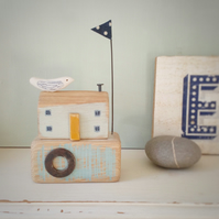 Wood seahouse with clay bird and spotty flag