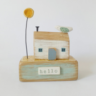 Wooden painted house with clay bird and flower 'hello'
