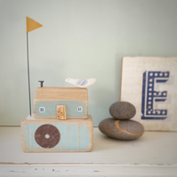 Little wooden seahouse with seabird and flag