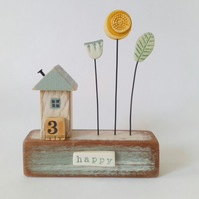 Little wooden house with clay flower garden 'happy'