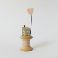 Little wooden house with clay heart on vintage bobbin