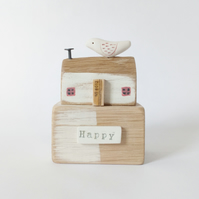 Wooden home with clay bird 'happy' house