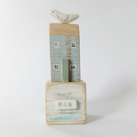 Little wooden house with clay bird on a vintage toy block