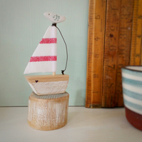 Handmade little wooden sail boat with clay bird