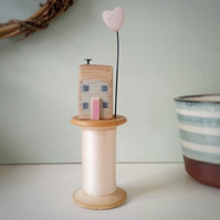 Tiny oak house with clay heart on vintage wooden bobbin
