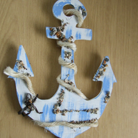 Decorative ships anchor wallhanging in blue with pebbles and sea shells.