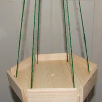 Little wooden hexagonal hanging bird table on twine for wild or garden birds.