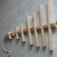 Toy for a caged bird, made from different sized round pieces of smooth pine.