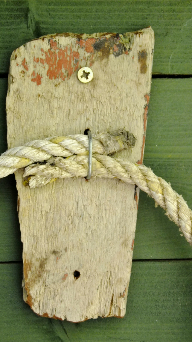 Rustic driftwood towel holder for bathroom or toilet with old rope.