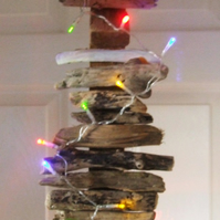 Illuminated driftwood wallhanging decoration with curling ribbon for Christmas