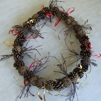 Christmas wreath with natural twigs & fir cones decorated with curling ribbon.