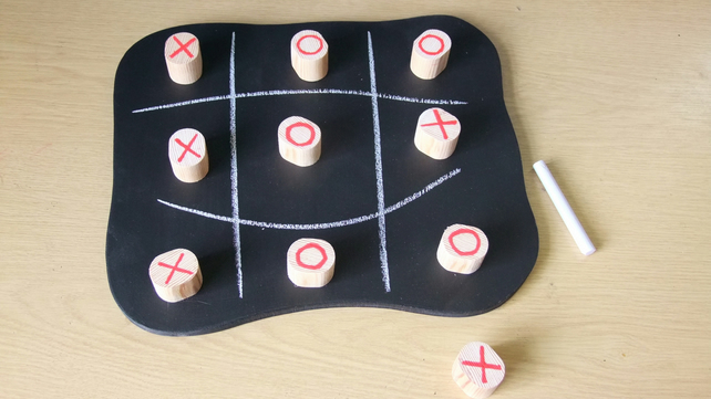 Noughts & Crosses game on a wooden chalk board with large wooden pieces.