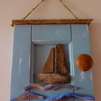 Sailing boat or dinghy mounted in a reclaimed door panel with driftwood waves