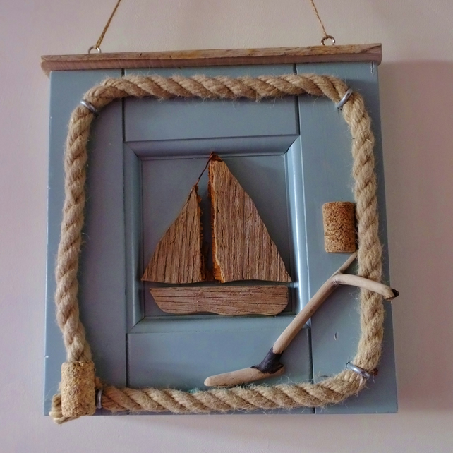 Little sailing boat or dinghy mounted in a reclaimed door panel with rope.