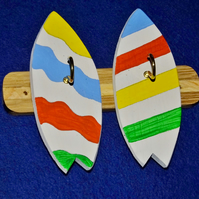 Key rack or holder with two brass hooks on colourful surfboards or bodyboards.