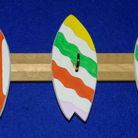 Key rack  holder with three brass hooks on colourful surfboards or bodyboards.