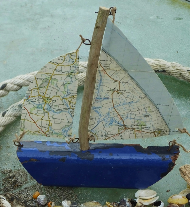 Blue hull driftwood sailing ship yacht with ordnance survey map sails