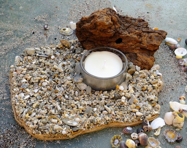 Pebble beach scene with glass tealight holder & tealight & driftwood backdrop.