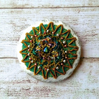 Ornate embroidered brooch.